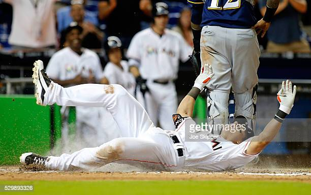 Derek Dietrich of the Miami Marlins scores following his seventhinning triple against the Milwaukee Brewers at Marlins Park on May 9 2016 in Miami...