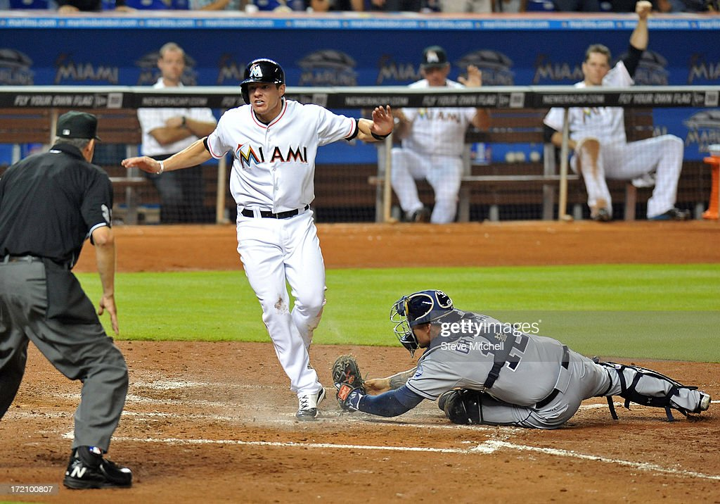 Derek Dietrich #51 of the Miami Marlins slides home safety past <a gi-track='captionPersonalityLinkClicked' href=/galleries/search?phrase=Yasmani+Grandal&family=editorial&specificpeople=7510522 ng-click='$event.stopPropagation()'>Yasmani Grandal</a> #12 of the San Diego Padres during the sixth inning at Marlins Park on July 1, 2013 in Miami, Florida.