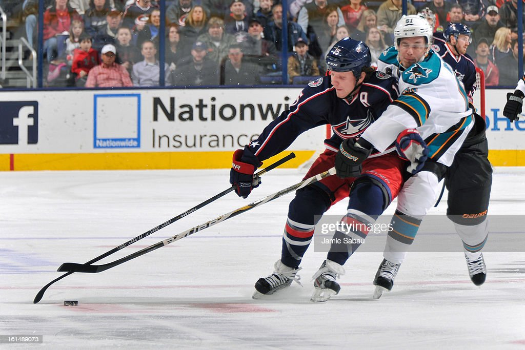 Derek Dorsett #15 of the Columbus Blue Jackets and Justin Braun #61 of the San Jose Sharks battle for control of a loose puck during the first period on February 11, 2013 at Nationwide Arena in Columbus, Ohio.