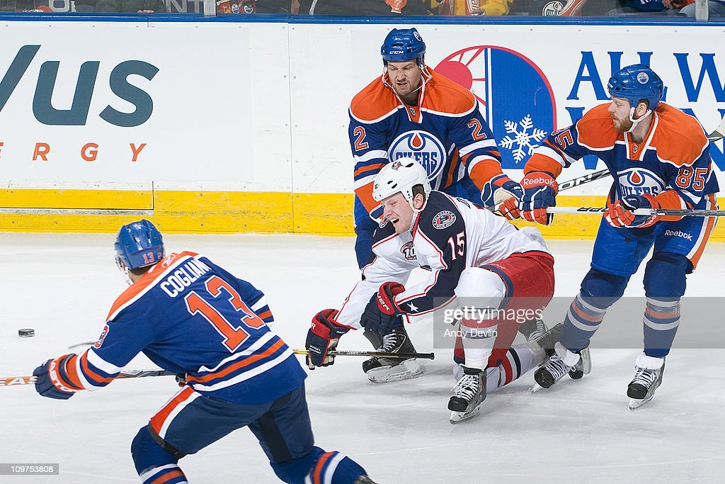Derek Dorsett #15 of the Columbus Blue Jackets is taken down by Jim Vandermeer #2 and Liam Reddox #85 of the Edmonton Oilers at Rexall Place on March 3, 2011 in Edmonton, Alberta, Canada.