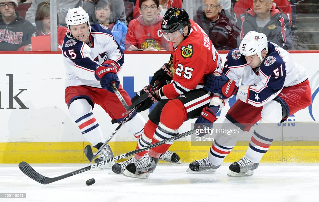 <a gi-track='captionPersonalityLinkClicked' href=/galleries/search?phrase=Derek+Dorsett&family=editorial&specificpeople=4306277 ng-click='$event.stopPropagation()'>Derek Dorsett</a> #15 of the Columbus Blue Jackets reaches across <a gi-track='captionPersonalityLinkClicked' href=/galleries/search?phrase=Viktor+Stalberg&family=editorial&specificpeople=5802237 ng-click='$event.stopPropagation()'>Viktor Stalberg</a> #25 of the Chicago Blackhawks as they chase after the puck, while <a gi-track='captionPersonalityLinkClicked' href=/galleries/search?phrase=Fedor+Tyutin&family=editorial&specificpeople=215245 ng-click='$event.stopPropagation()'>Fedor Tyutin</a> #51 of the Blue Jackets reaches from behind, during the NHL game on December 26, 2011 at the United Center in Chicago, Illinois.