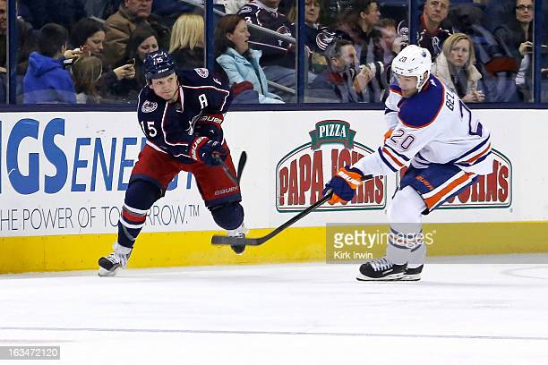 Derek Dorsett of the Columbus Blue Jackets shoots the puck past Eric Belanger of the Edmonton Oilers on March 5 2013 at Nationwide Arena in Columbus...