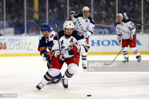 Derek Dorsett of the New York Rangers controls the puck against the New York Islanders during the 2014 Coors Light NHL Stadium Series at Yankee...