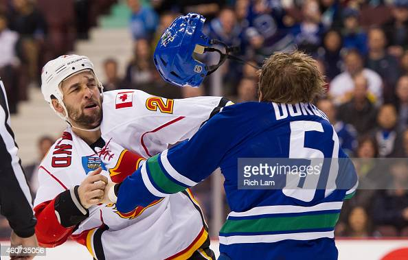 Derek Dorsett of the Vancouver Canucks and Deryk Engelland of the Calgary Flames fight during the first period in NHL action on December 20 2014 at...