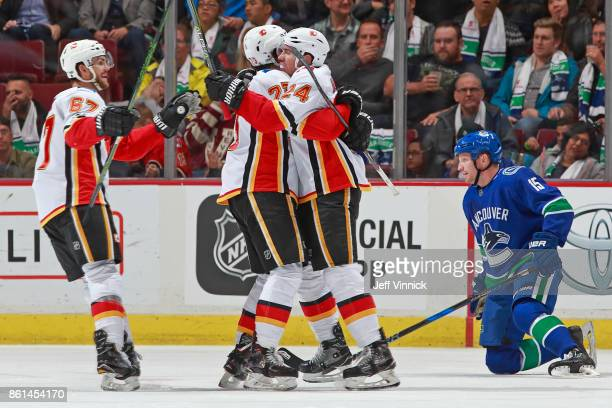 Derek Dorsett of the Vancouver Canucks looks on as Sean Monahan of the Calgary Flames is congratulated by teammate Travis Hamonic after scoring...