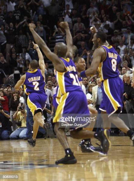 Derek Fisher leads Gary Payton and Kobe Bryant of the Los Angeles Lakers off the floor after Fisher made the gamewinning shot with 4 seconds...