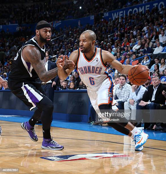 Derek Fisher of the Oklahoma City Thunder drives the ball around DeMarcus Cousins of the Sacremento Kings during an NBA game on January 19 2014 at...