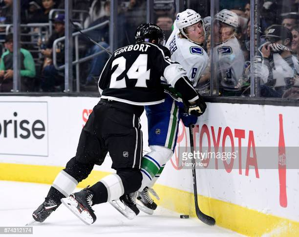 Derek Forbort of the Los Angeles Kings cecks Brock Boeser of the Vancouver Canucks into the boards during the first period at Staples Center on...