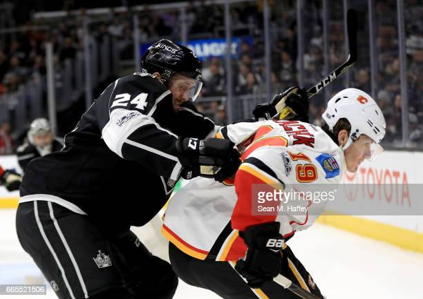 Derek Forbort of the Los Angeles Kings cross checks Matthew Tkachuk of the Calgary Flames during the third period of a game at Staples Center on...