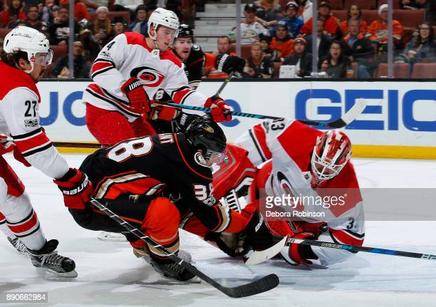 Derek Grant of the Anaheim Ducks puts the puck on net for a goal against Scott Darling Justin Faulk and Haydn Fleury of the Carolina Hurricanes...
