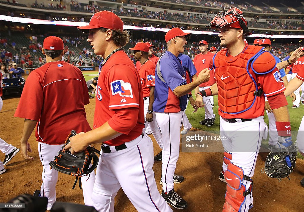 Derek Holland #45 and catcher <a gi-track='captionPersonalityLinkClicked' href=/galleries/search?phrase=A.J.+Pierzynski&family=editorial&specificpeople=204486 ng-click='$event.stopPropagation()'>A.J. Pierzynski</a> #12 of the Texas Rangers walk off the field after Holland pitched a shutout against the Houston Astros at Rangers Ballpark in Arlington on September 23, 2013 in Arlington, Texas.