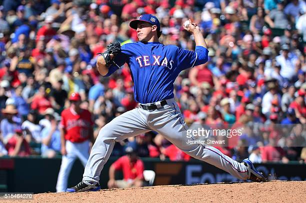 Derek Holland of the Texas Rangers delivers a pitch in the second inning against the Los Angeles Angels during the spring training game at Tempe...