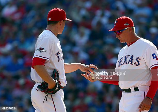 Derek Holland of the Texas Rangers hands over the ball to Manager Jeff Banister in the top of the third inning of Game 4 of the ALDS against the...