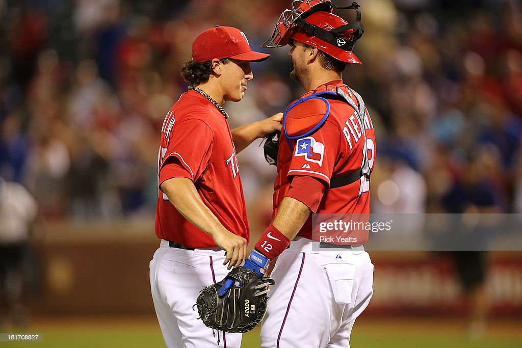 Derek Holland #45 of the Texas Rangers is congratulated by A.J. Pierzynski #12 for pitching a shutout against the Houston Astros at Rangers Ballpark in Arlington on September 23, 2013 in Arlington, Texas.