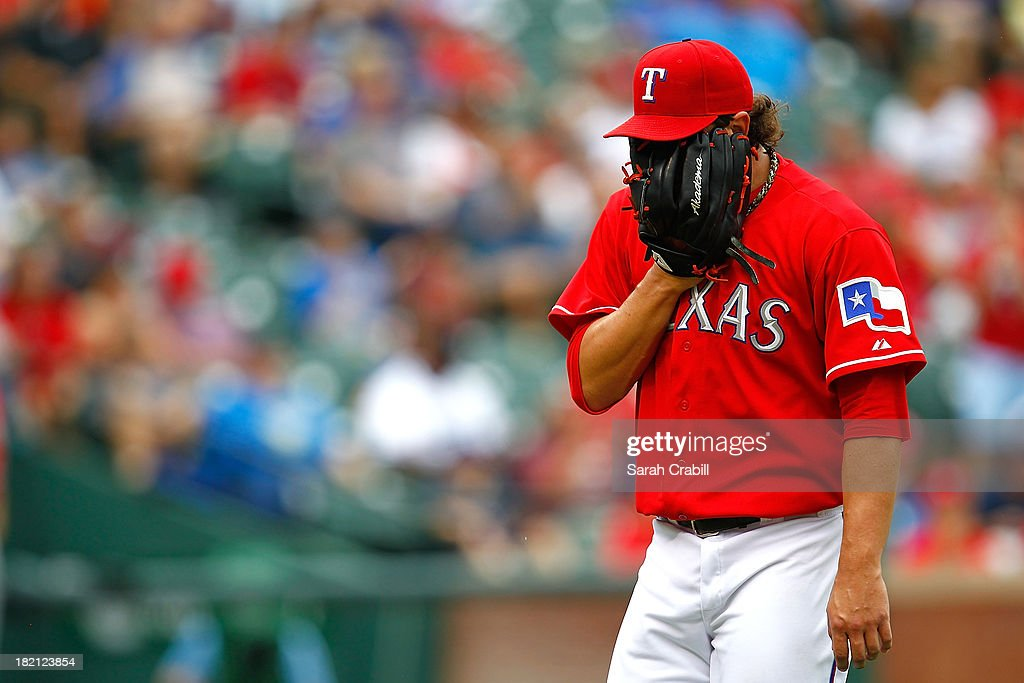 Derek Holland #45 of the Texas Rangers looks down after pitching during a game against the Los Angeles Angels of Anaheim at Rangers Ballpark in Arlington on September 28, 2013 in Arlington, Texas.