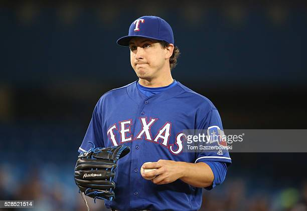 Derek Holland of the Texas Rangers looks on after giving up a run in the first inning during MLB game action against the Toronto Blue Jays on May 5...