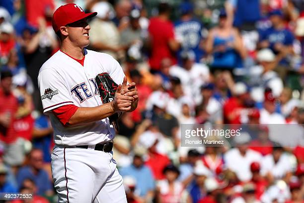 Derek Holland of the Texas Rangers reacts in the first inning against the Toronto Blue Jays in game four of the American League Division Series at...
