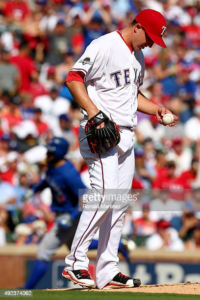 Derek Holland of the Texas Rangers reacts on the mound after allowing a solo home run to Kevin Pillar of the Toronto Blue Jays in game four of the...