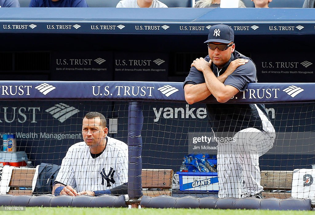 Derek Jeter #2 (R) and Alex Rodriguez #13 of the New York Yankees look on from the dugout in the ninth inning against the Detroit Tigers at Yankee Stadium on August 11, 2013 in the Bronx borough of New York City.