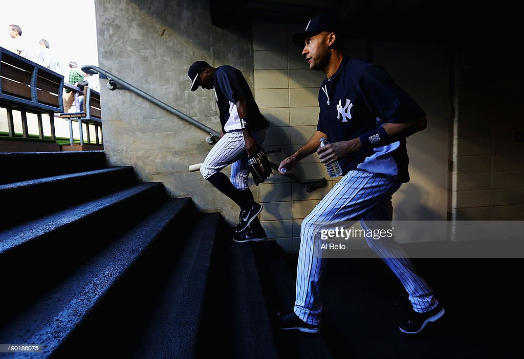 Derek Jeter #2 and Alfonso Soriano #12 of the New York Yankees walk on the field for batting practice before their game against the New York Mets at Yankee Stadium on May 13, 2014 in the Bronx borough of New York City.