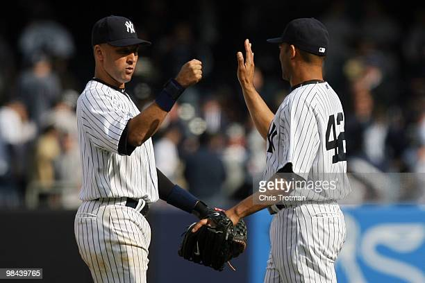 Derek Jeter and Mariano Rivera of the New York Yankees celebrate after defeating the Los Angeles Angels of Anaheim during the Yankees home opener at...