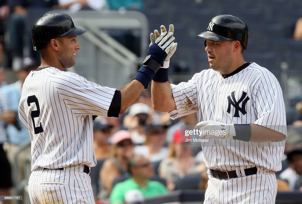 Derek Jeter #2 and Nick Johnson #36 of the New York Yankees celebrate after scoring in the seventh inning against the Chicago White Sox after a double from teammate Mark Teixeira (not pictured) on May 2, 2010 at Yankee Stadium in the Bronx borough of New York City. The Yankees defeated the White Sox 12-3.