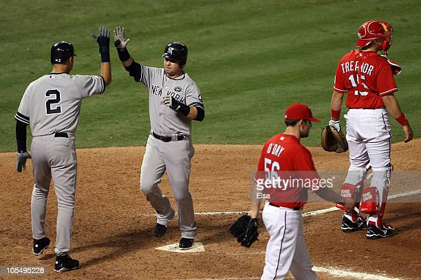 Derek Jeter and Nick Swisher of the New York Yankees celebrate after scoring in the eighth inning as Darren O'Day and Matt Treanor of the Texas...