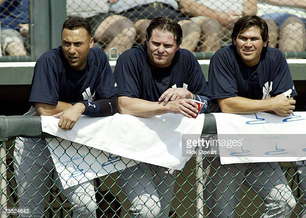 Derek Jeter Jason Giambi and Johnny Damon of the New York Yankees watch play from the dugout against the Atlanta Braves during a Spring Training game...