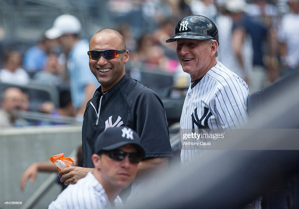 Derek Jeter #2 of the New York Yankees and first base coach Mick Kelleher #50 smile in the dugout during the game against the Detroit Tigers at Yankee Stadium on Thursday, August 7, 2014 in the Bronx borough of New York City.