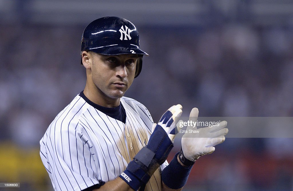 Derek Jeter of the New York Yankees applauds after Bernie Williams hits a three run home run in the eighth inning of game one of the American League...