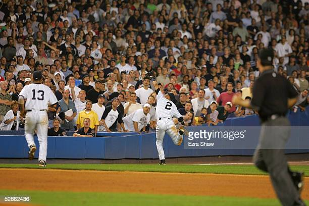 Derek Jeter of the New York Yankees catches a foul ball before he dives into the stands in the 12th inning of the game against the Boston Red Sox on...
