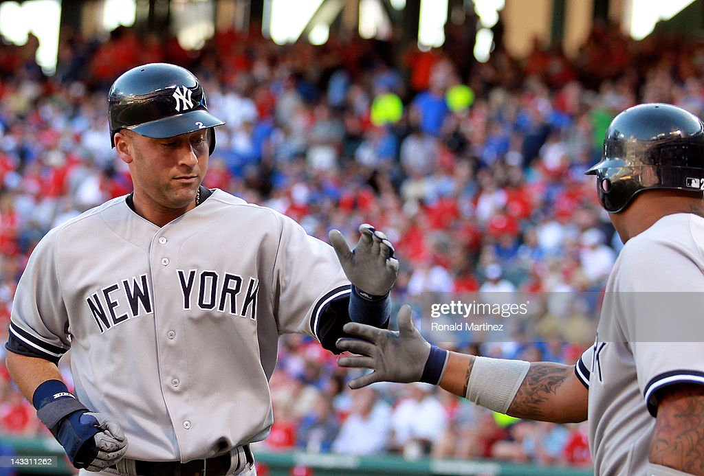 <a gi-track='captionPersonalityLinkClicked' href=/galleries/search?phrase=Derek+Jeter&family=editorial&specificpeople=167125 ng-click='$event.stopPropagation()'>Derek Jeter</a> #2 of the New York Yankees celebrates a run with Andruw Jones #22 against the Texas Rangers in the first inning at Rangers Ballpark in Arlington on April 23, 2012 in Arlington, Texas.