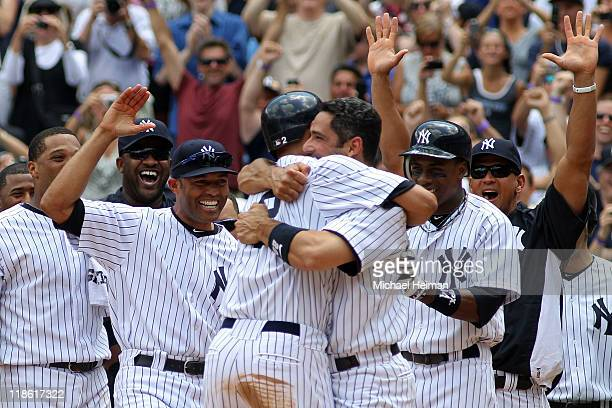 Derek Jeter of the New York Yankees celebrates at home with teammates Jorge Posada Mariano Rivera Alex Rodriguez and Curtis Granderson after hitting...