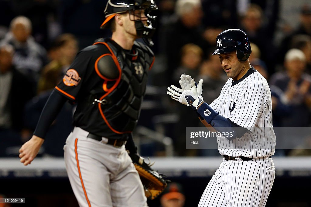 Derek Jeter #2 of the New York Yankees celebrates while scoring in the sixth inning past Matt Wieters #32 of the Baltimore Orioles during Game Five of the American League Division Series at Yankee Stadium on October 12, 2012 in New York, New York.