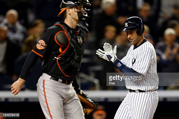 Derek Jeter of the New York Yankees celebrates while scoring in the sixth inning past Matt Wieters of the Baltimore Orioles during Game Five of the...