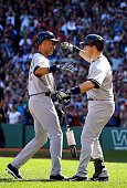 Derek Jeter of the New York Yankees celebrates with Mark Teixeira after hitting a single for his last career at bat in the third inning against the...