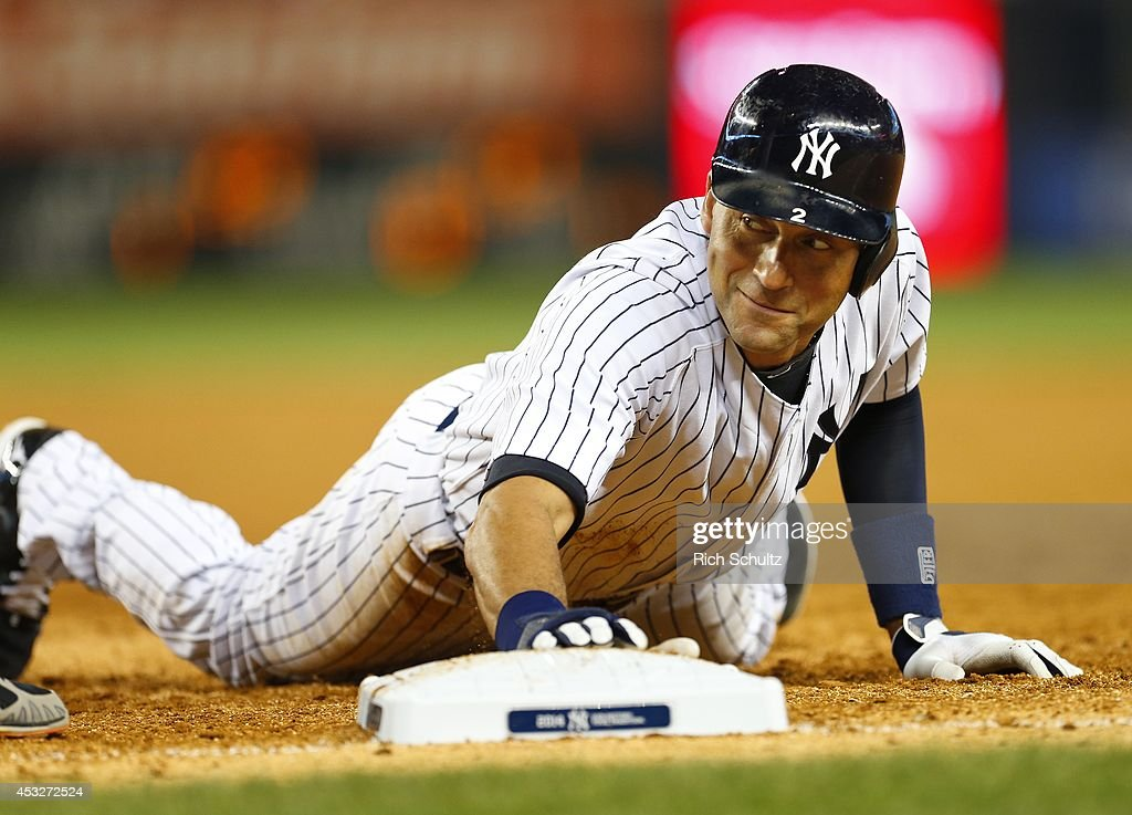 Derek Jeter of the New York Yankees dives safely back to first base on a pickoff attempt during the sixth inning against the Detroit Tigers in a MLB...