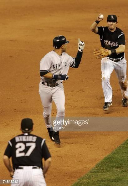 Derek Jeter of the New York Yankees gets caught in a rundown between second and third by shortstop Troy Tulowitzki and third baseman Garrett Atkins...