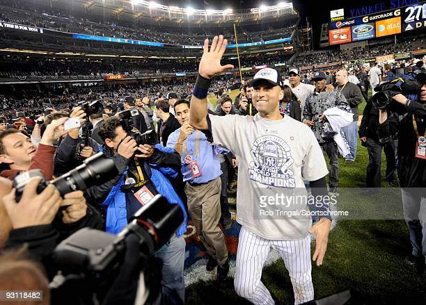 Derek Jeter of the New York Yankees holds up five fingers for all his championships after defeating the Philadelphia Phillies slides in during Game...