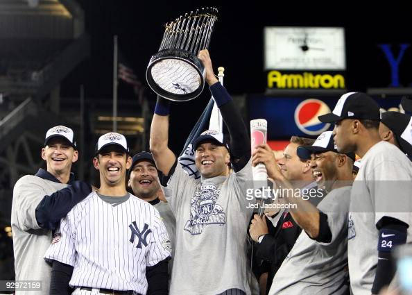 Derek Jeter of the New York Yankees holds up the trophy as he celebrates with AJ Burnett Jorge Posada Mariano Rivera and Robinson Cano after their 73...
