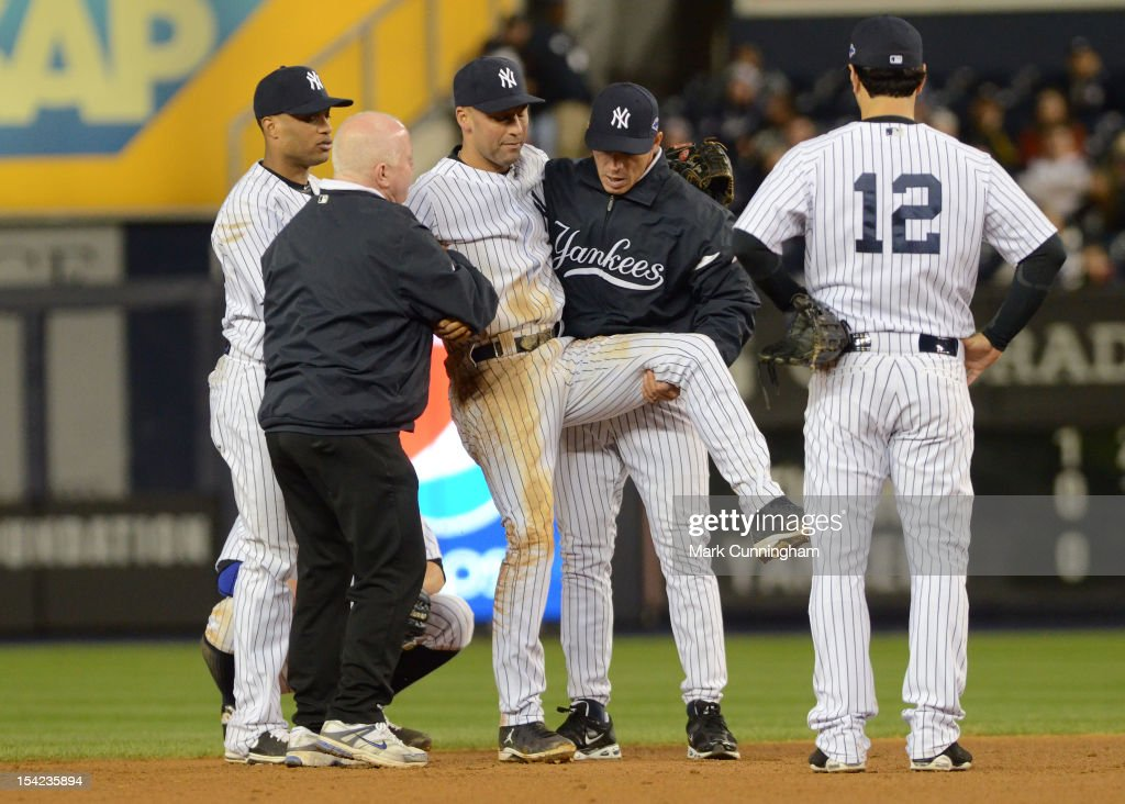 Derek Jeter #2 of the New York Yankees is carried off the field by trainer Steve Donohue (L) and manager Joe Girardi #28 after Jeter fractured his left ankle in the top of the 12th inning against the Detroit Tigers during Game One of the American League Championship Series at Yankee Stadium on October 13, 2012 in New York City. The Tigers defeated the Yankees 6-4 in 12 innings.