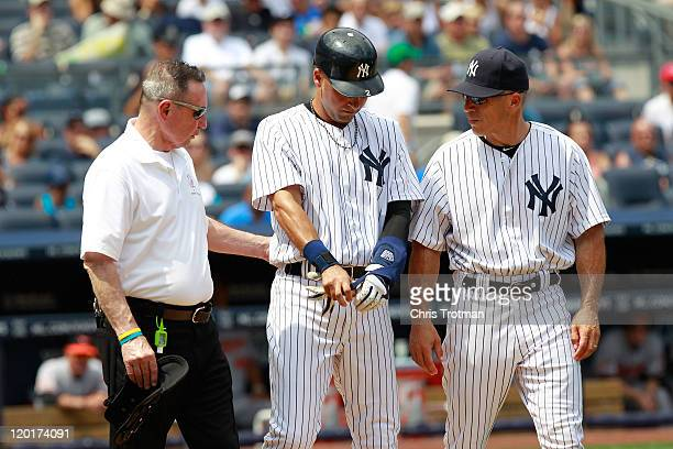 Derek Jeter of the New York Yankees is checked on by the trainer Gene Monahan and his manager Joe Girardi after being hit on the hand by a pitch in...