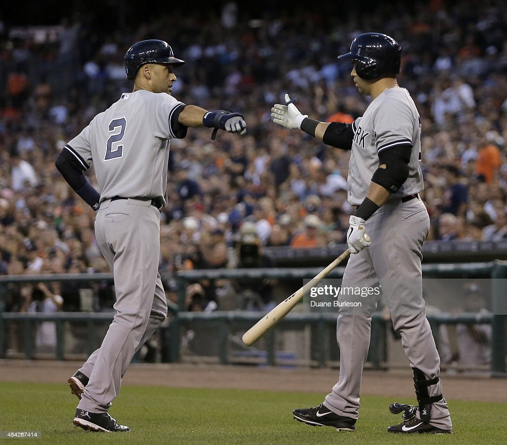 Derek Jeter #2 of the New York Yankees is congratulated by Carlos Beltran #36 of the New York Yankees after scoring in the third inning on a double by Mark Teieira against the Detroit Tigers at Comerica Park on August 27, 2014 in Detroit, Michigan.