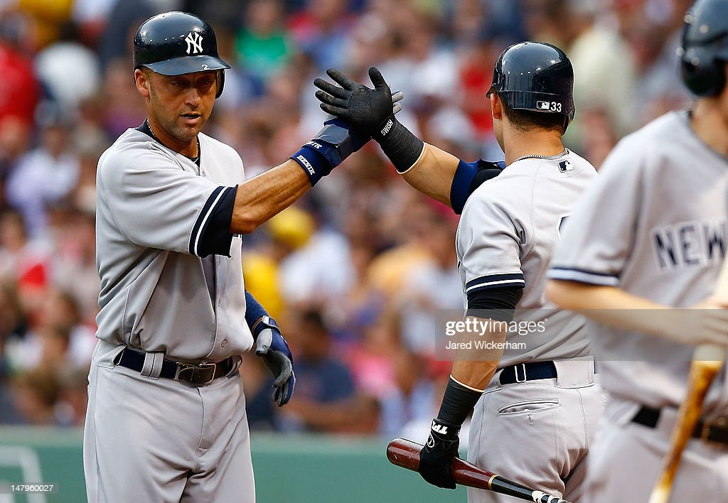 Derek Jeter #2 of the New York Yankees is congratulated by teammate Nick Swisher #33 after scoring against the Boston Red Sox in the first inning during the game on July 6, 2012 at Fenway Park in Boston, Massachusetts.