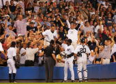 Derek Jeter of the New York Yankees is helped out of the crowd after he made a diving catch in the 12th inning of their game against the Boston Red...