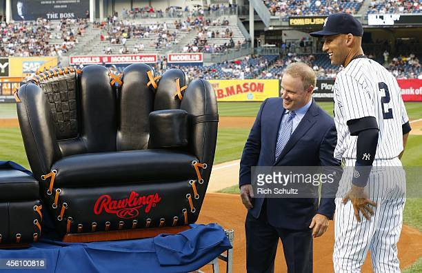 Derek Jeter of the New York Yankees is presented with a chair molded after his Rawlings baseball glove before the start of a game against the Boston...