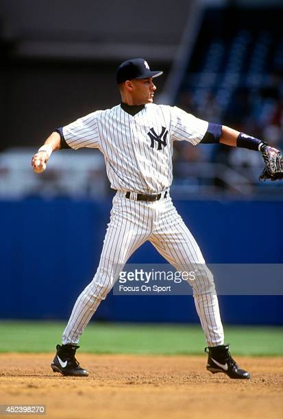 Derek Jeter of the New York Yankees is sets to make a throw to first base during an Major League Baseball game circa 1996 at Yankee Stadium in the...
