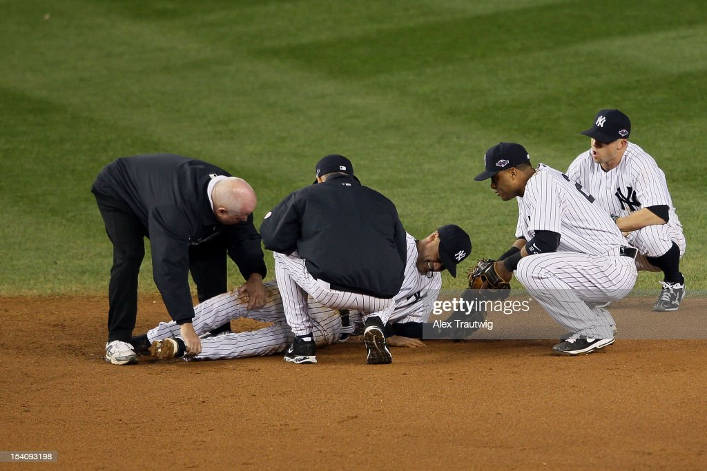 Derek Jeter #2 of the New York Yankees is tended to by trainer Steve Donohue (L), manager Joe Girardi (C), Robinson Cano #24 and Brett Gardner #11 (R) of the New York Yankees after Jeter hurt his leg in the top of the 12th inning against the Detroit Tigers during Game One of the American League Championship Series at Yankee Stadium on October 13, 2012 in the Bronx borough of New York City, New York.