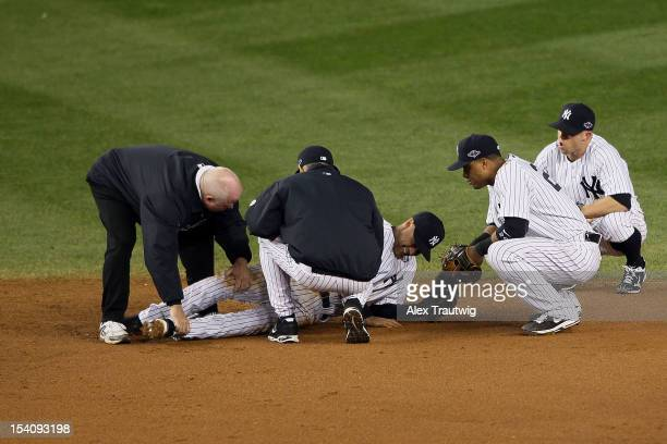Derek Jeter of the New York Yankees is tended to by trainer Steve Donohue manager Joe Girardi Robinson Cano and Brett Gardner of the New York Yankees...