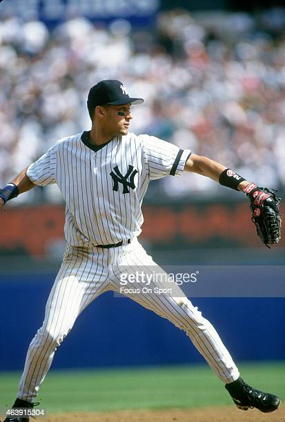 Derek Jeter of the New York Yankees looks to throw the ball to first base during an Major League Baseball game circa 1996 at Yankee Stadium in the...